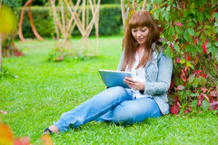 Young woman reading in tablet pc Royalty Free Stock Image