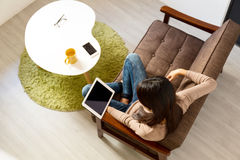 Young woman reading on tablet pc at home Royalty Free Stock Photo