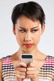 Young Woman Reading Text Message With Annoyed Expression Stock Photo