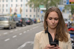 Young woman reading a text message on her mobile. Grimacing a pulling a dubious expression as she reads the text in an urban street, closeup head and shoulders Royalty Free Stock Photo