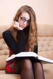 Young woman reading thick book on a sofa Stock Photography