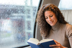 Young woman reading on a train Royalty Free Stock Photo