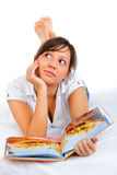 Young woman reading travel magazine Royalty Free Stock Images