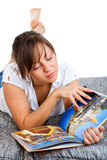 Young woman reading travel magazine Stock Photography