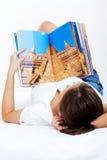 Young woman reading travel magazine Stock Photo