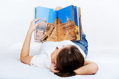 Young woman reading travel magazine Royalty Free Stock Photos