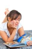 Young woman reading travel magazine Stock Photos