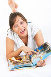 Young woman reading travel magazine Stock Images