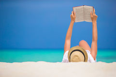 Young woman is reading on tropical white beach Royalty Free Stock Image