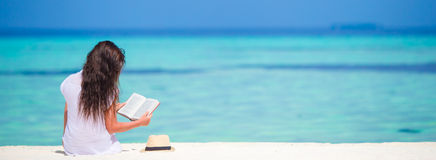 Young woman reading on tropical white beach Stock Photos