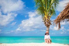 Young woman reading on tropical white beach near palm tree Stock Photo