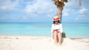 Young woman reading on tropical white beach near palm tree. Young woman reading on tropical white beach stock video footage