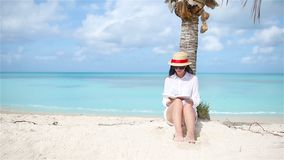 Young woman reading on tropical white beach near palm tree. Young woman reading on tropical white beach stock footage