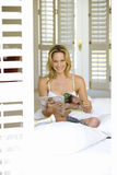 Young woman reading in underwear by shutters, smiling, portrait Stock Images