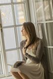 Young woman reading by window Stock Photo