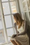 Young woman reading by window Stock Images