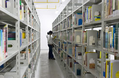 Young woman reads in aisles in a public library. Young woman reads in the aisles in a public library with shelves full of books - isolated over white.The woman's Stock Images