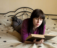 The young woman reads the book. Lying on a bed Royalty Free Stock Photography