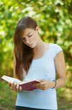Young woman reads book Stock Image