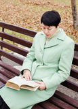 Young woman reads the book in autumn park Stock Images