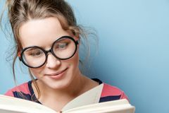 Young woman reads a book on a blue background Stock Image