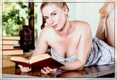 Young woman reads a book lying on a desk in front of a window. old style, lolita concept royalty free stock image