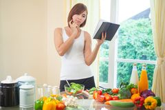 Young woman reads cookbook Stock Photography