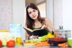 Young  woman reads cookbook for recipe. At kitchen Stock Photos
