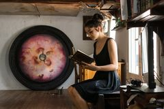 Young woman reads in her painting studio royalty free stock photos