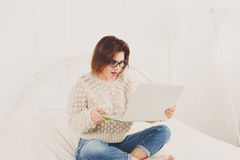 Young woman reads from laptop in bed, high key. Young woman looks into laptop computer surprised, delighted, emotional. Girl in eyeglasses. Attractive woman in Royalty Free Stock Photo