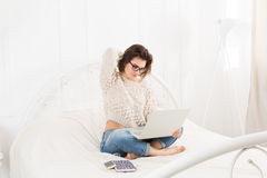 Young woman reads from laptop in bed, high key Stock Images