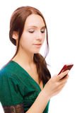 Young woman reads message. Young woman in green dress reads message on mobile phone, on white background Royalty Free Stock Images