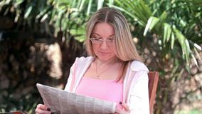 Young woman reads the newspaper. Young woman reads announcements in the newspaper stock video footage