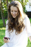 Young woman reads sms. Young pretty woman reads sms on mobile phone, outdoors Stock Photo