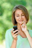 Young woman reads sms on mobile. Smiling beautiful young woman reads sms on mobile phone, against background of summer green park Stock Photos