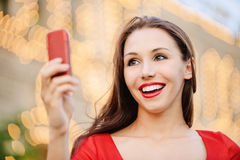 Young woman reads text message. Young charming woman in red dress reads text message on mobile phone and laughs Stock Image