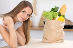 Young woman is ready for cooking in a kitchen. Big paper bag full of fresh vegetables and fruits is standing at the. Table near housewife looking at the camera Royalty Free Stock Image