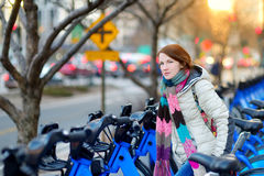 Young woman ready to rent a bike in New York. Young beautiful woman ready to rent a city bike in New York, USA Royalty Free Stock Photography