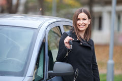 Young woman ready to travel. Beautiful young woman standing by the car with car keys Royalty Free Stock Image