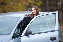 Young woman ready to travel. Beautiful young woman standing by the car with car keys Stock Photo