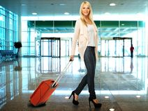 Young woman ready to travel. Blond woman with suitcase in airport Royalty Free Stock Photography