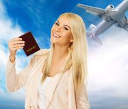 Young woman ready to travel. Happy blond woman with passport against blue sky with plane Stock Photography