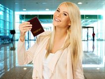 Young woman ready to travel. Happy blond woman with passport  in airport Stock Image