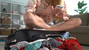A young woman is ready to travel. She sitting on a crowded suitcase and using a smartphone. A young woman is ready to travel. She sitting on the crowded suitcase stock video footage
