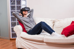 Young woman realxing on the couch and having fun playing a virtu Stock Image