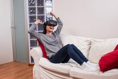 Young woman realxing on the couch and having fun playing a virtu Stock Photo