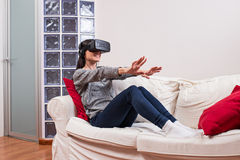 Young woman realxing on the couch and having fun playing a virtu Stock Photography