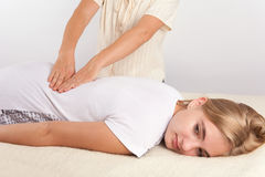 Young woman receives bowen therapy fro her back Royalty Free Stock Photos