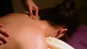 A young woman receives a massage from a man`s hands in a room with a dark light. Close-up. Soft focus.  stock video footage