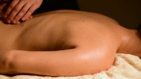 A young woman receives a massage from a man`s hands in a room with a dark light. Close-up. Soft focus.  stock video